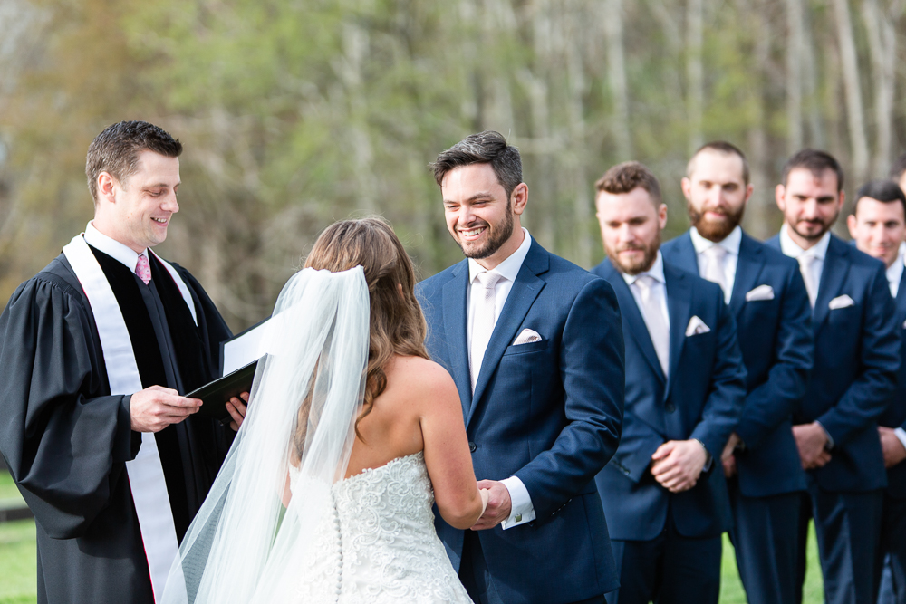 Candid picture of groom smiling during the outdoor wedding ceremony in Charlottesville, Virginia