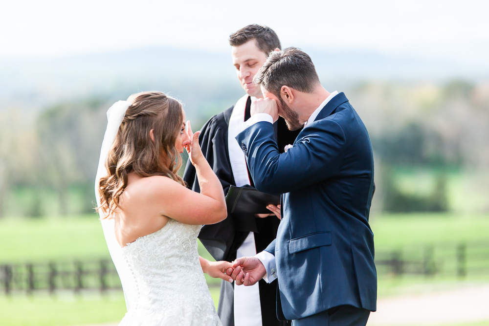 Both bride and groom wiping away tears during an emotional wedding ceremony at the Lodge at Mount Ida Farm