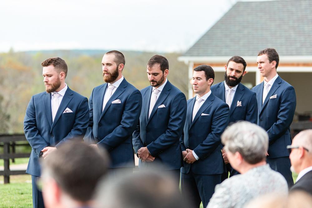 Groomsmen in navy suits standing during the outdoor wedding ceremony