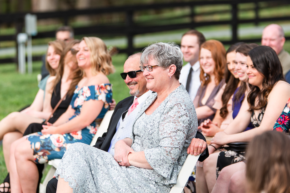 Candid picture of wedding guests smiling as the watch the wedding ceremony