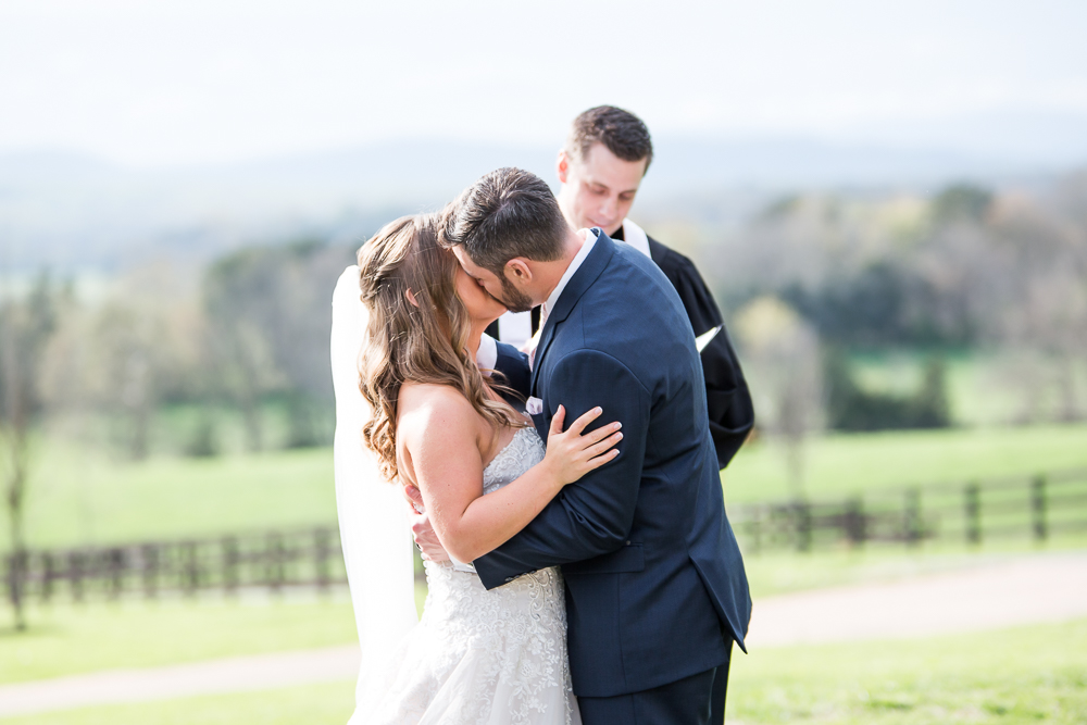 Bride and groom kiss at the end of the wedding ceremony