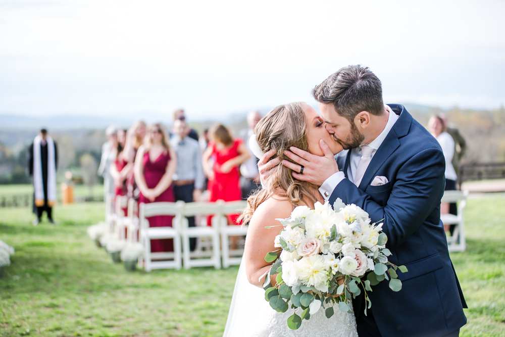 Husband and wife kiss at the end of the aisle after their wedding ceremony at the Lodge at Mount Ida Farm
