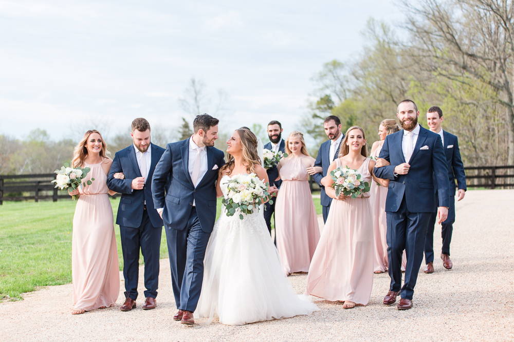 Blush and navy bridal party walking down the road to the Lodge at Mount Ida Farm