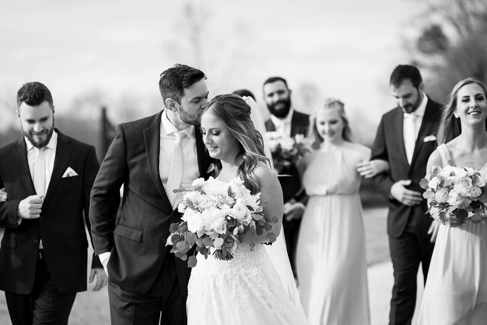 Black and white photo of sweet moment where groom kisses bride on the head