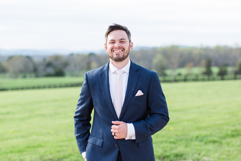 Smiling groom in navy suit at Mount Ida