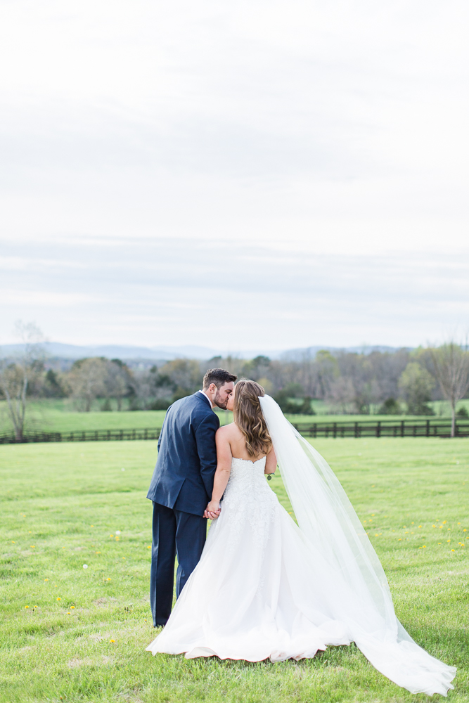 Bride and groom kiss as they walk away from the wedding venue   Charlottesville wedding venue