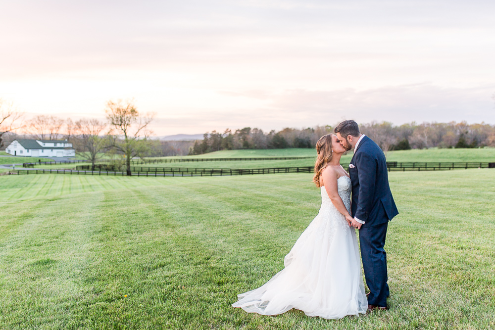 Wedding couple kisses during a beautiful sunset at the Lodge at Mount Ida Farm