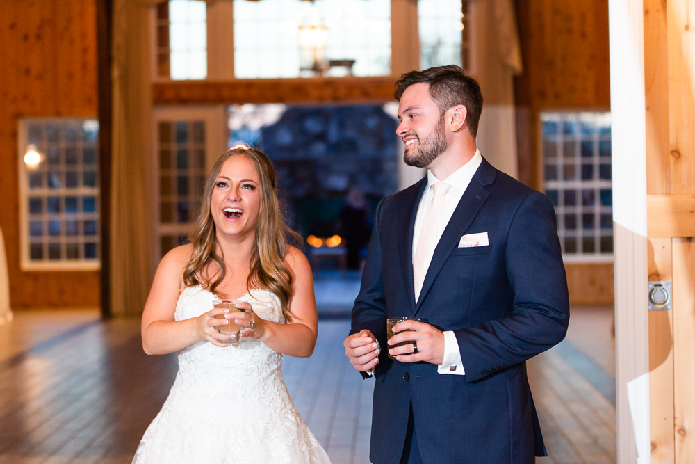 Candid photo of bride and groom laughing during their wedding reception