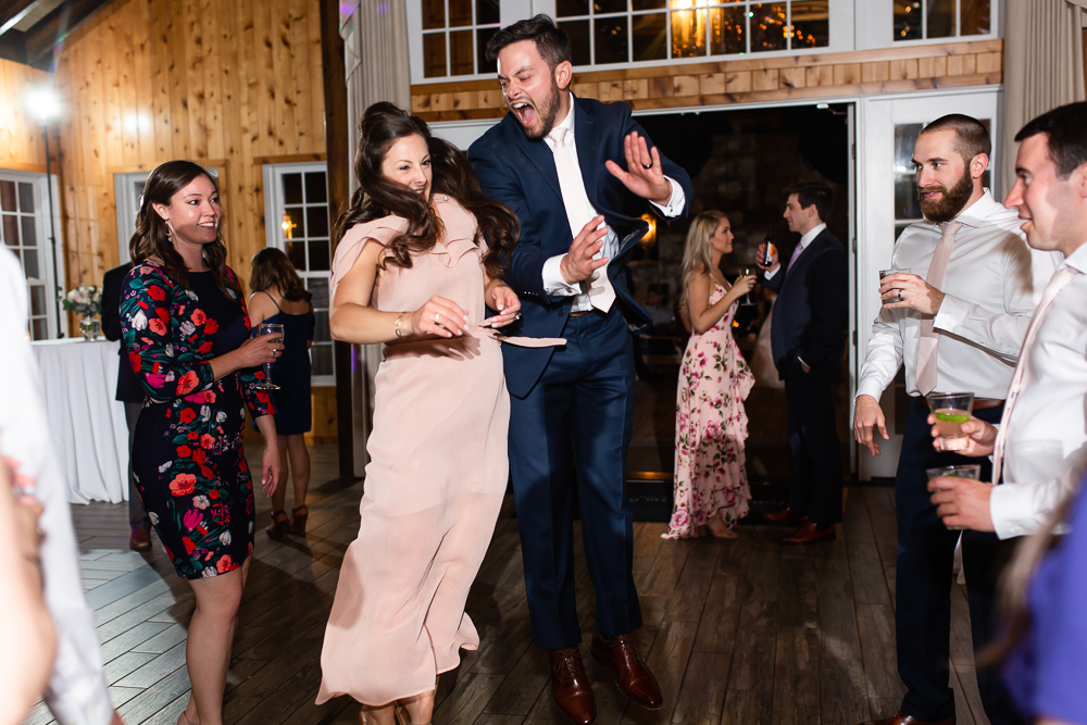 Groom and bridesmaid jumping in the air during the wedding reception