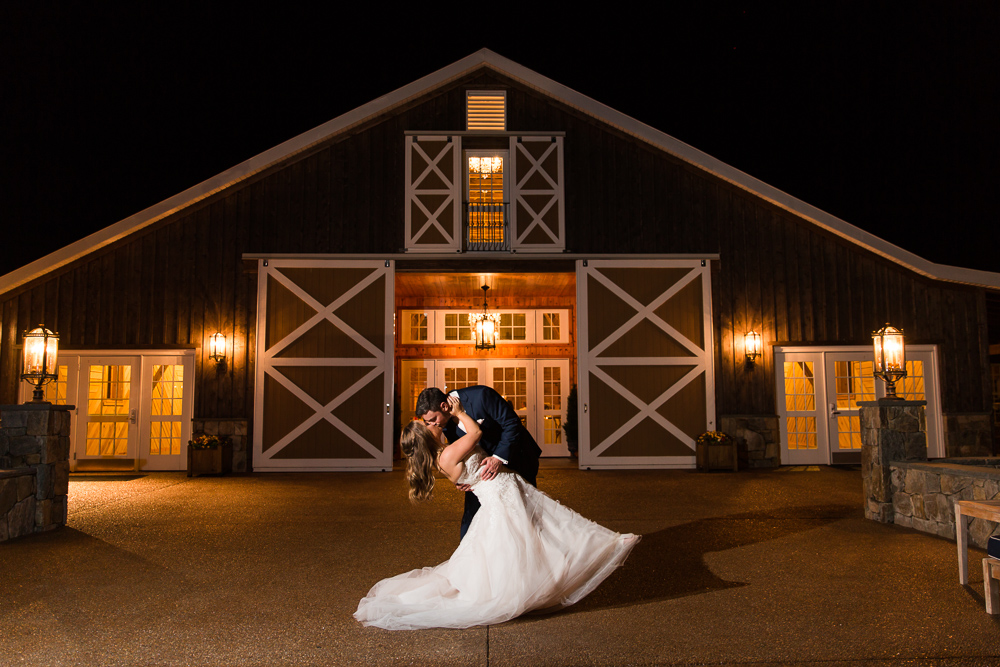 Bride and groom dip and kiss in front of the Lodge at Mount Ida Farm at night   Charlottesville, VA wedding venue