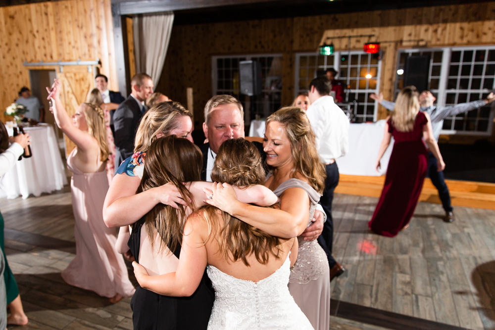 Bride and her family have a group hug on the dance floor