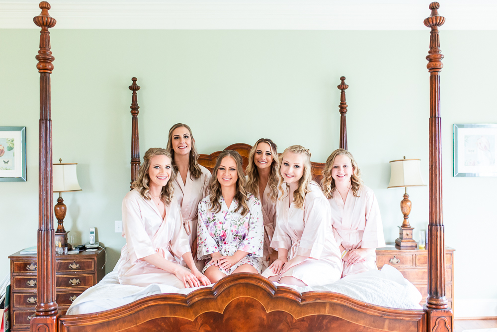 Bride and her bridesmaids in matching robes on the four-post bed at Mount Ida Farm