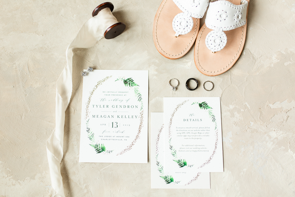 Flat-lay photo of wedding details with invitations, rings, and bride's shoes.