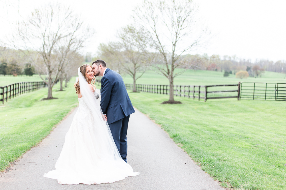 Groom giving bride a kiss on the cheek as they stand on the tree-lined road at Mount Ida Farm in Charlottesville, Virginia | Best Charlottesville wedding venue