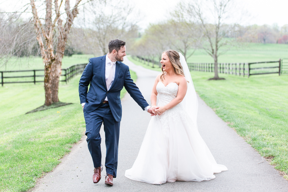 Candid wedding photo as couple laughs and walks along the road at Mount Ida Farm   Candid Charlottesville wedding photographer