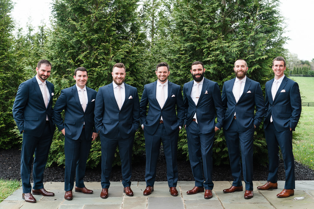 Groom with groomsmen lined up by the evergreen trees at Mount Ida Farm's Aventador