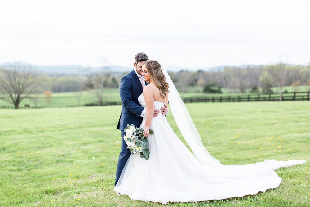 Wedding couple in the grass at the Lodge at Mount Ida Farm with Blue Ridge Mountains in the background