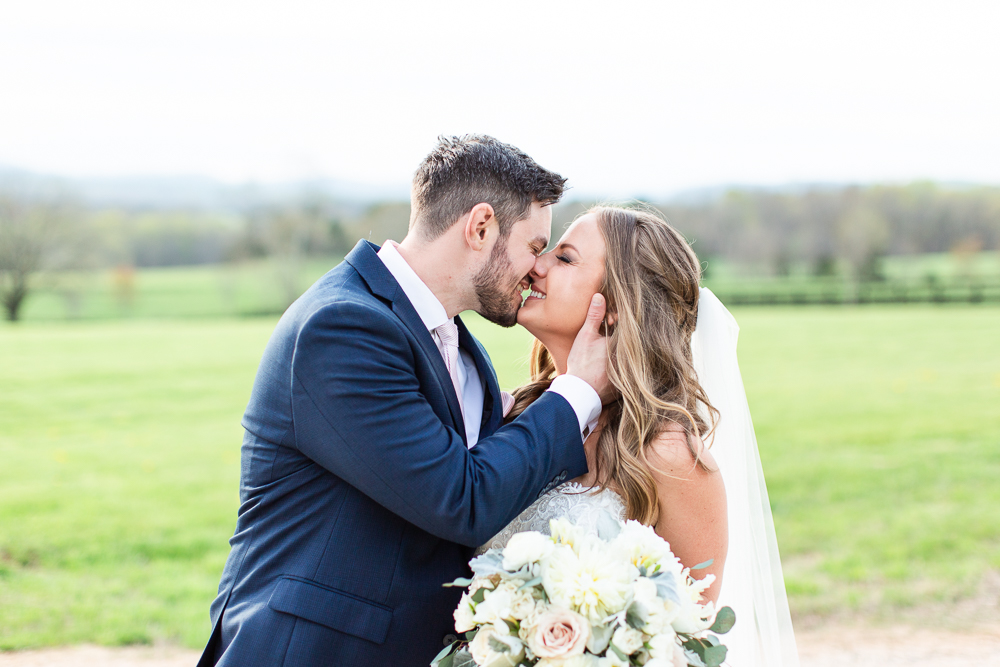 Bride and groom lean in for a kiss during wedding portraits at the Lodge at Mount Ida Farm