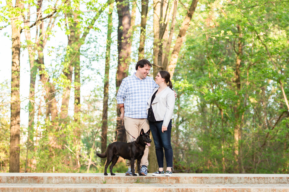 Engaged couple with their dog on the steps at Roosevelt Island, DC