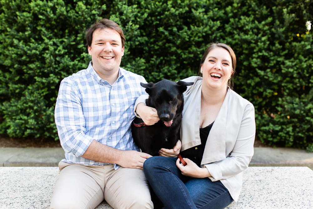 Laughing at their dog while sitting on a bench at Theodore Roosevelt Island