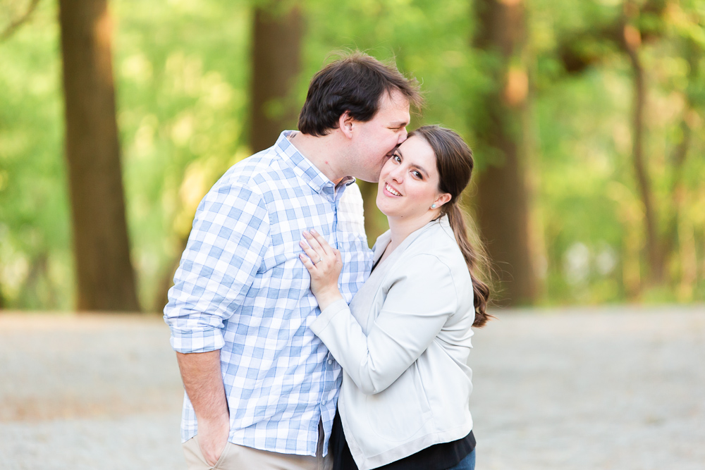 Groom-to-be giving his fiancee a kiss on the cheek, with green trees behind them | Roosevelt Island engagement pictures