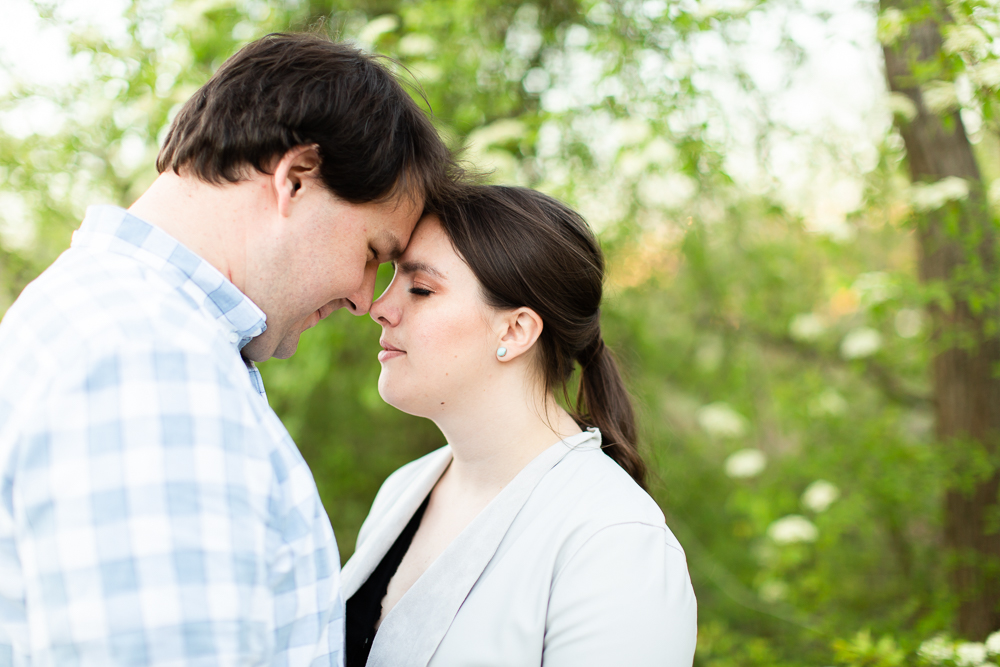 Couple leans in forehead to forehead while hiking on Theodore Roosevelt Island during their engagement pictures
