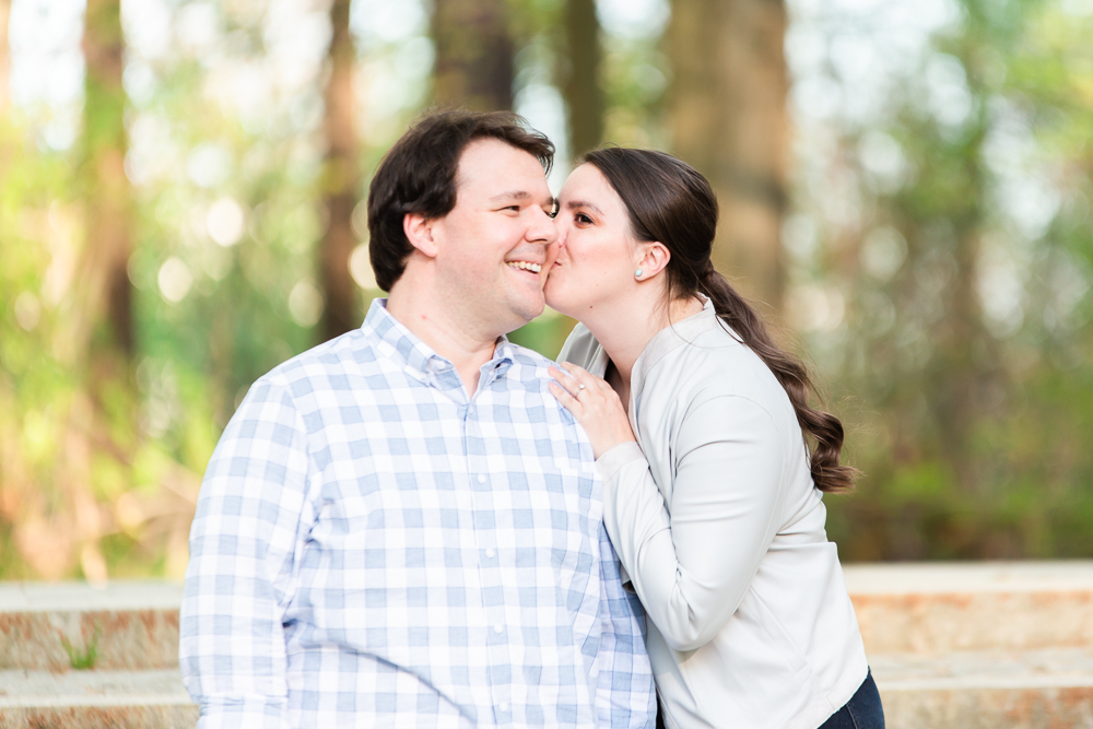 Bride-to-be kissing her fiance on the cheek during Washington, DC engagement session