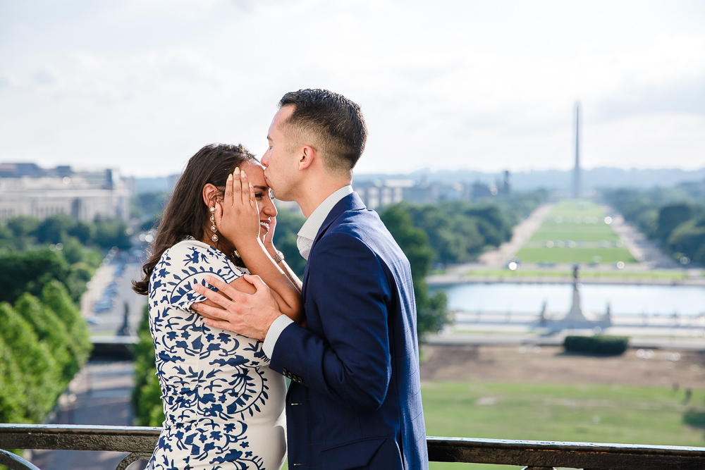 Giving his surprised fiancee a kiss on the forehead after popping the question | U.S. Capitol surprise proposal and engagement photography