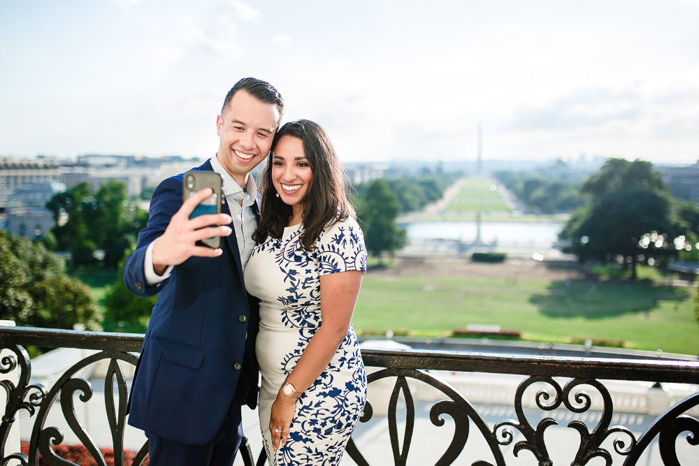 Happy couple taking a selfie with the National Mall behind them after getting engaged | Washington, DC engagement photographer