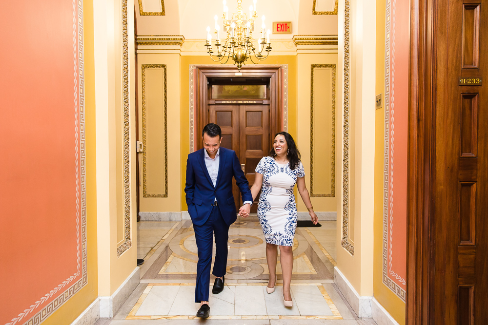 Engaged couple holding hands as they walk through the halls of the Capitol Building during their engagement session