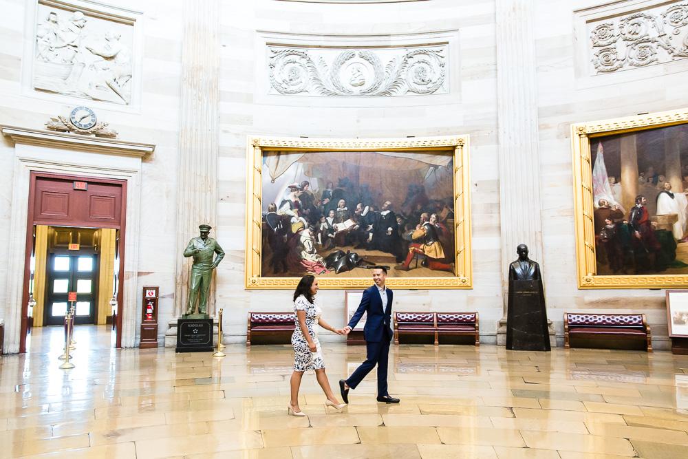 Engaged couple walking though the United States Capitol rotunda in Washington, DC | DC engagement photo locations