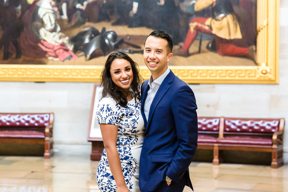 Smiling engaged couple in the U.S. Capitol Building rotunda after their proposal