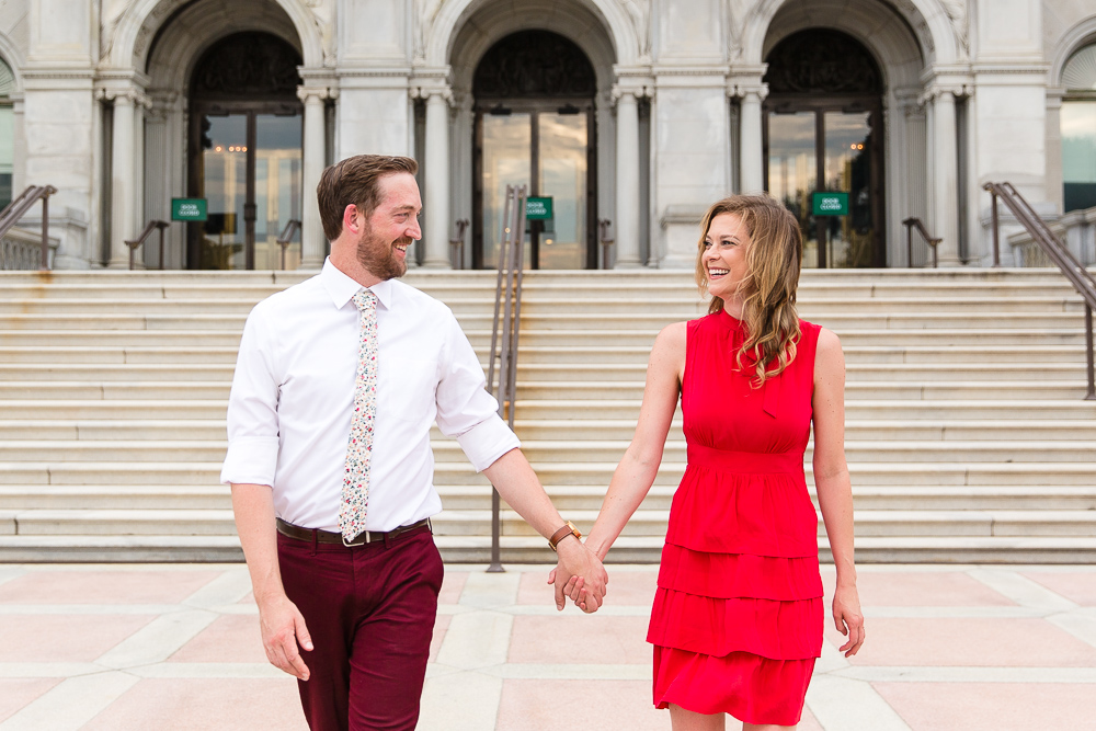 Candid engagement photos in front of the stairs at the Library of Congress