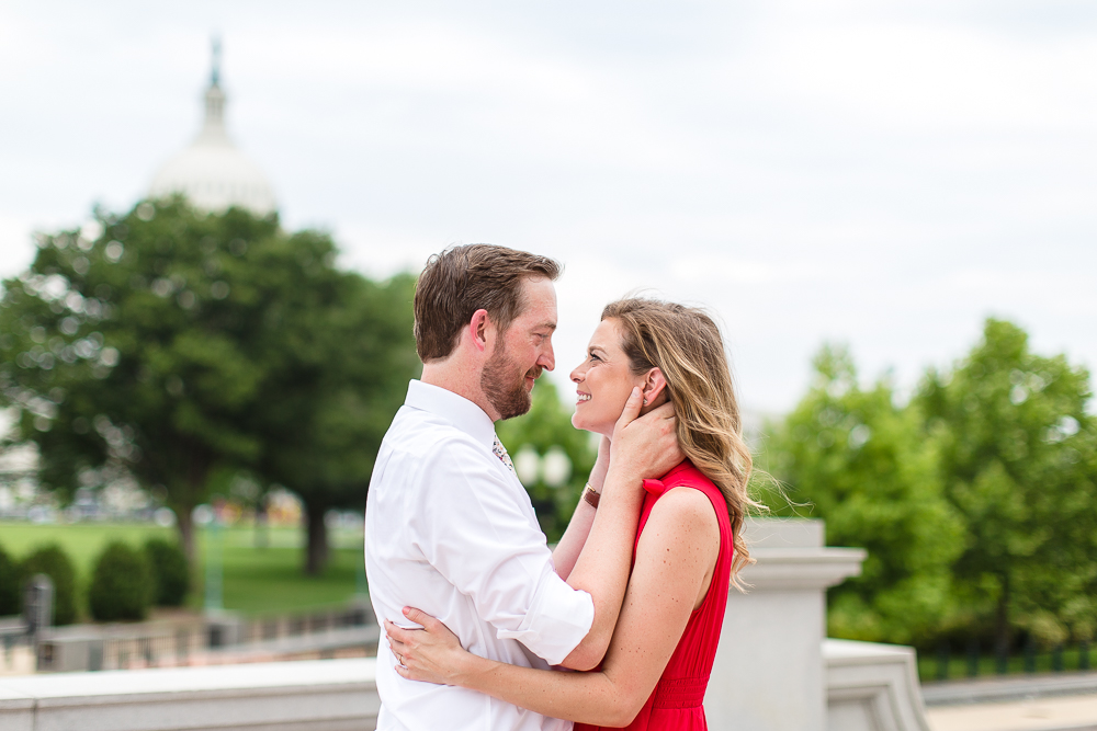 Engaged couple cuddling with the U.S. Capitol in the background