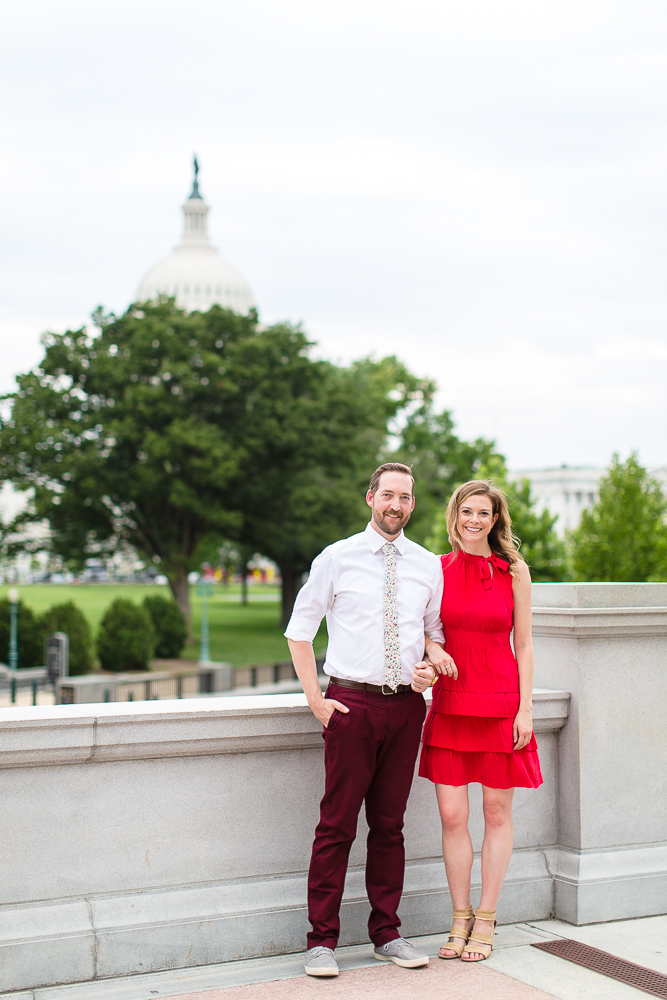Smiling engaged couple on the patio of the Library of Congress with Capitol Building behind them