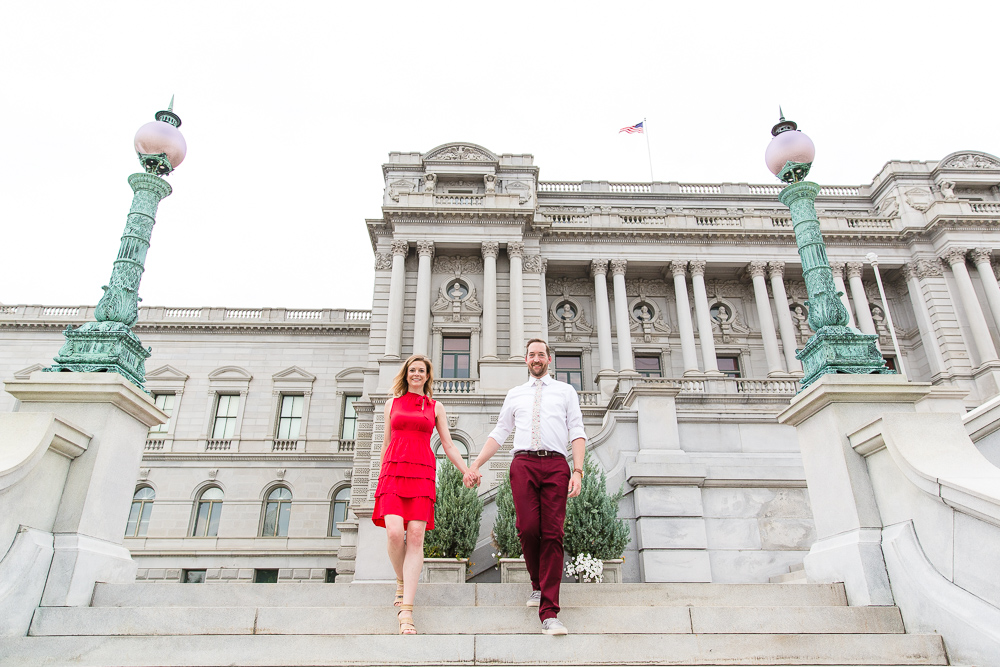 Holding hands and walking down the steps of the Library of Congress during a DC engagement session