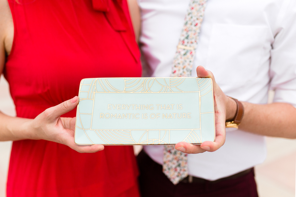 """Engagement photo holding tray that says """"Everything that is romantic is of nature"""""""