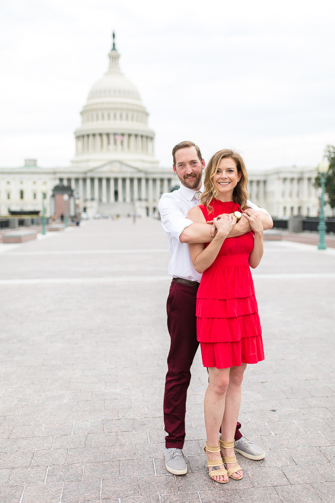 Happy couple smiling in front of the U.S. Capitol Building during their DC engagement session