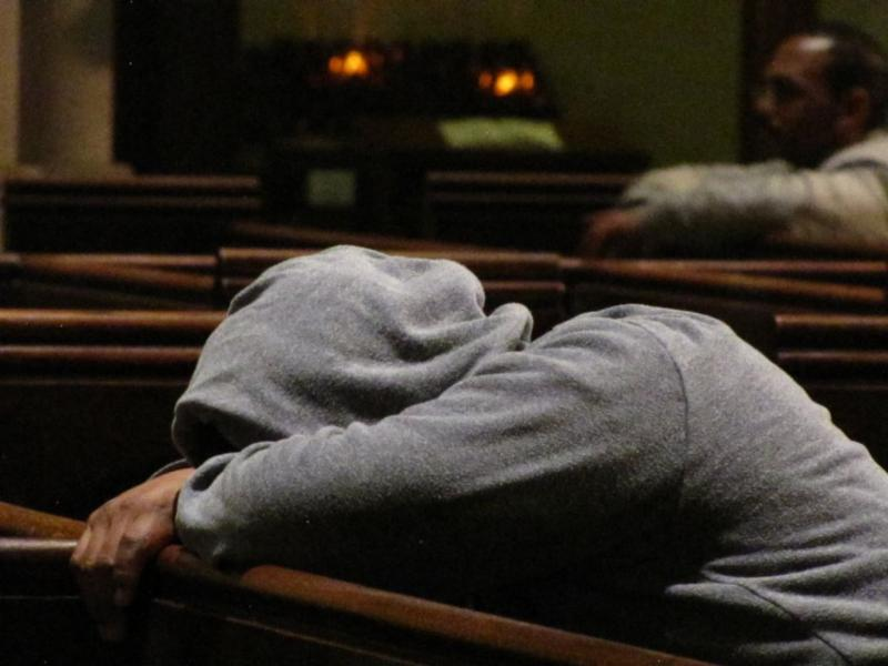 One of the many who rest in Saint Mary's whenever our doors are open. In the background a parishioner prays.