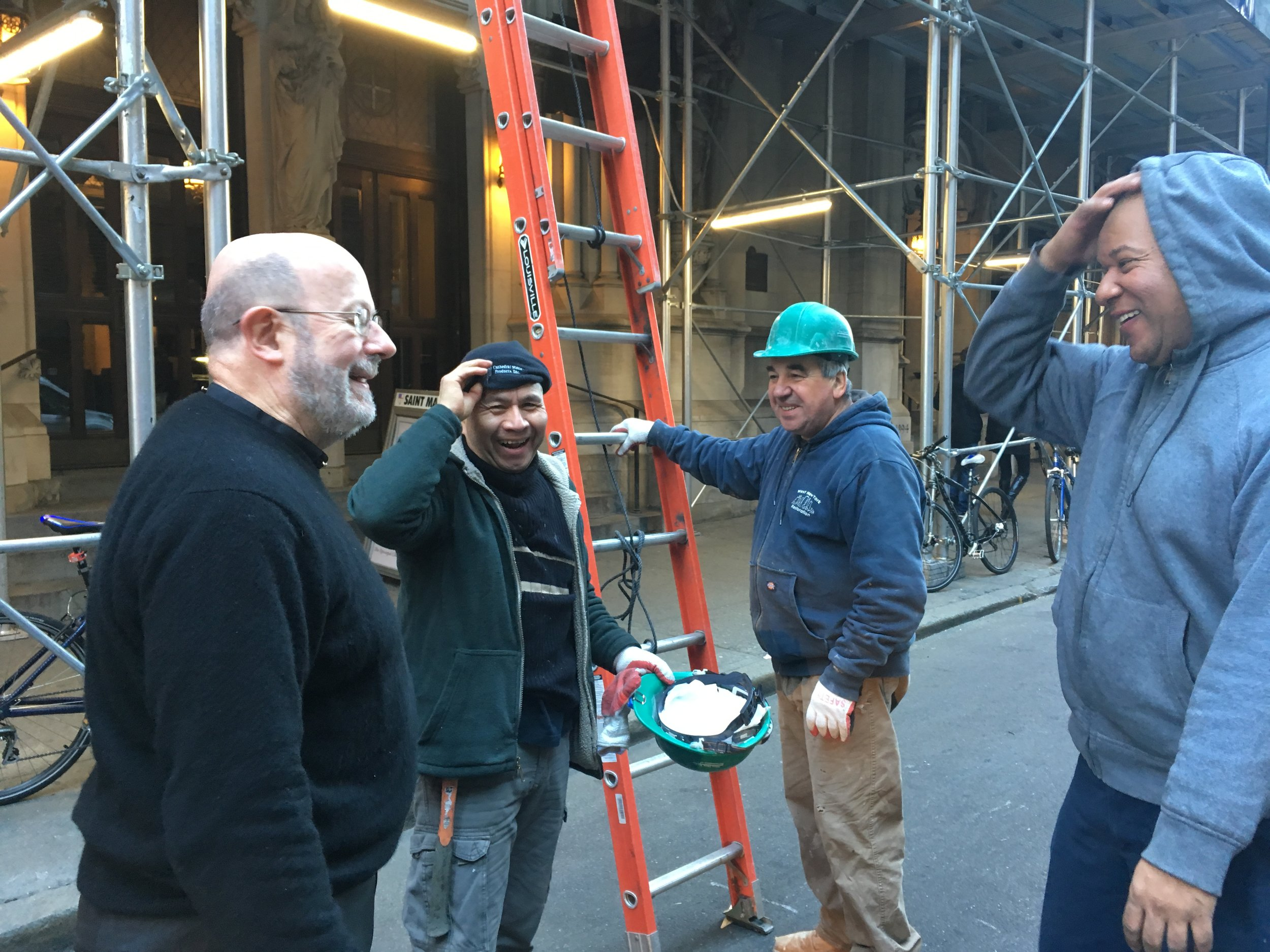 Father Smith (left) and Sexton Mario Martinez (right) with West New York crew members who helped put up the new banners.