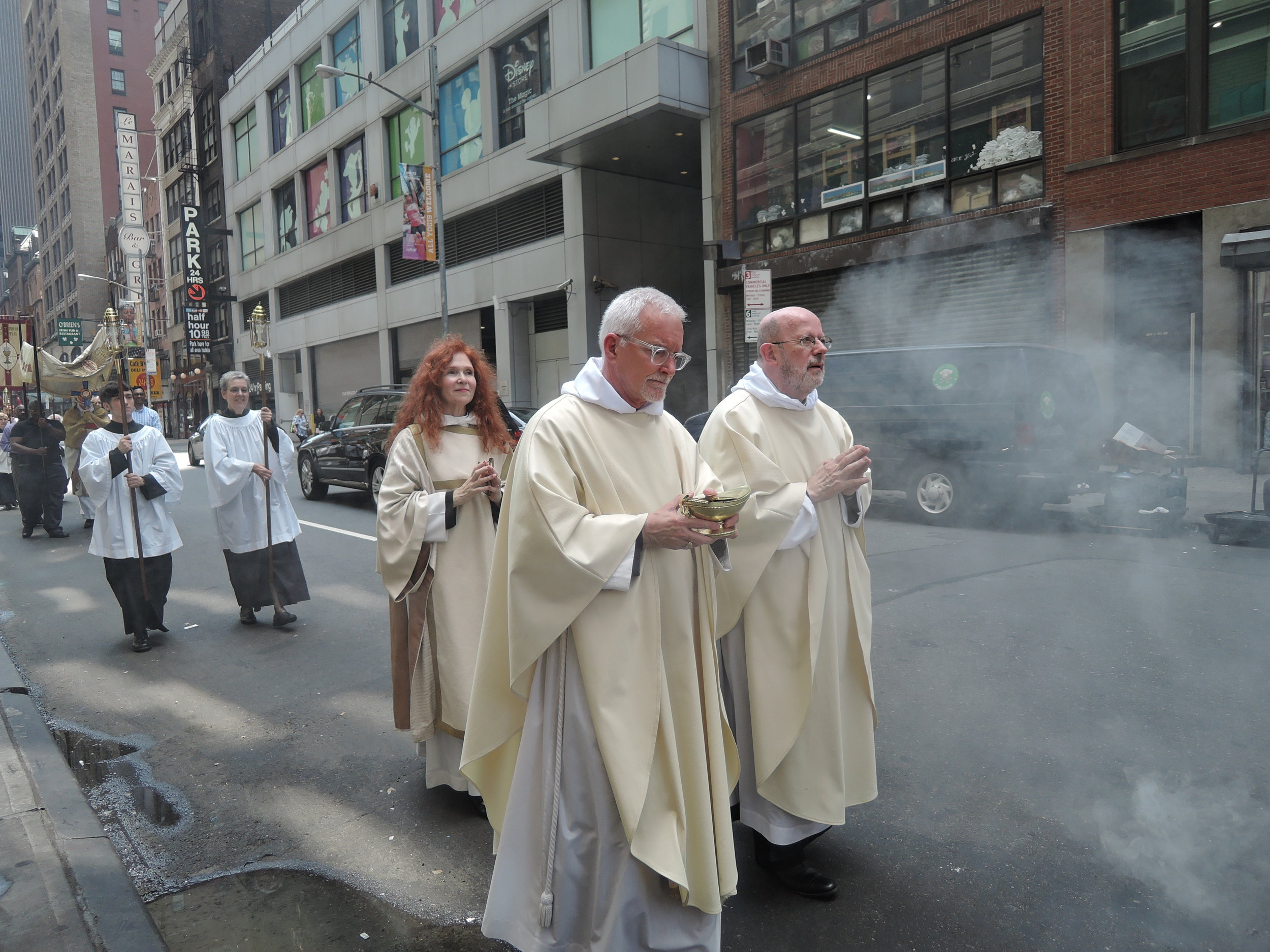 Assisting clergy in procession, following the thurifers