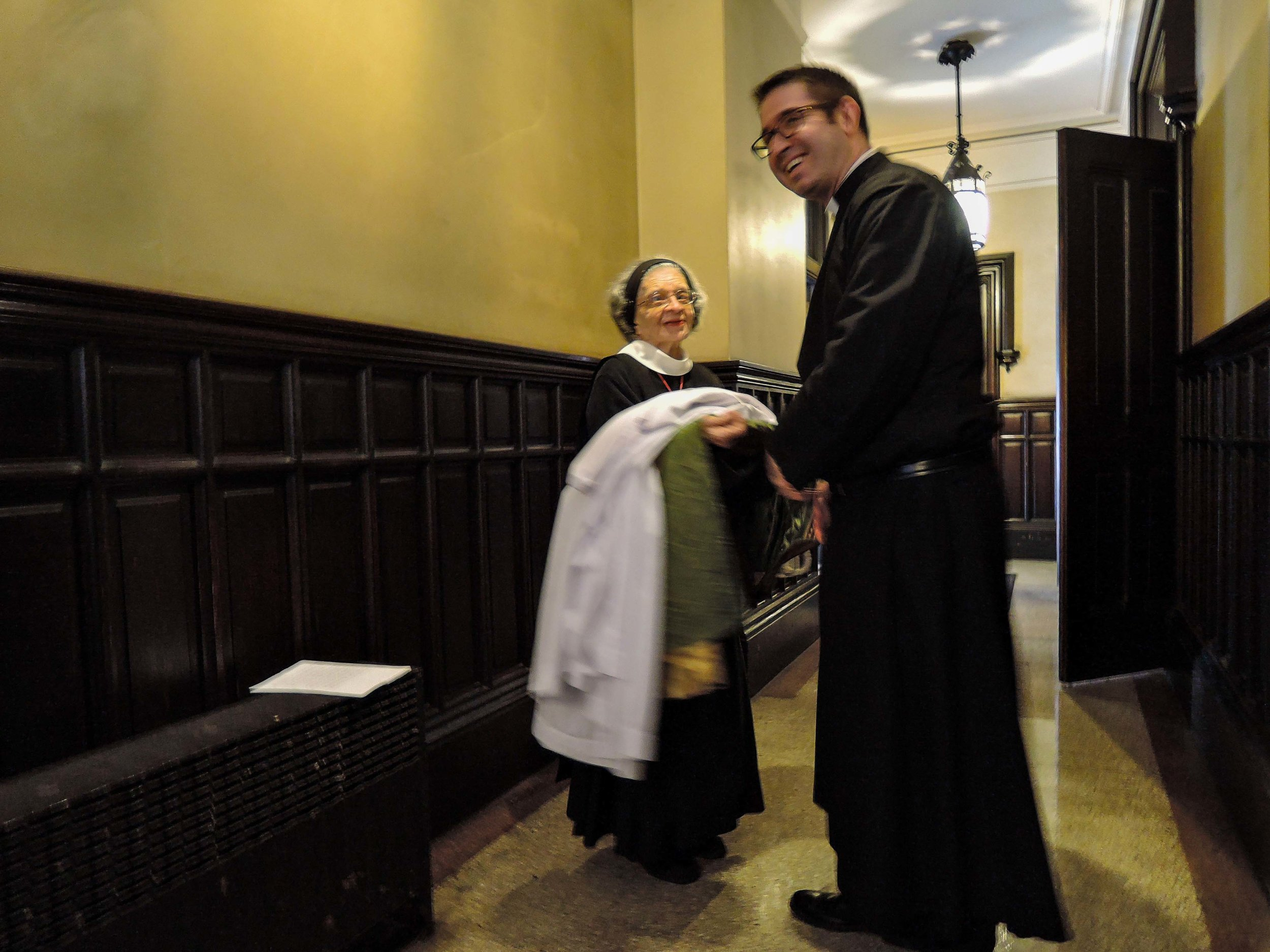 Sr. Laura Katharine assists Fr. Jacobson with his vestments after Mass.