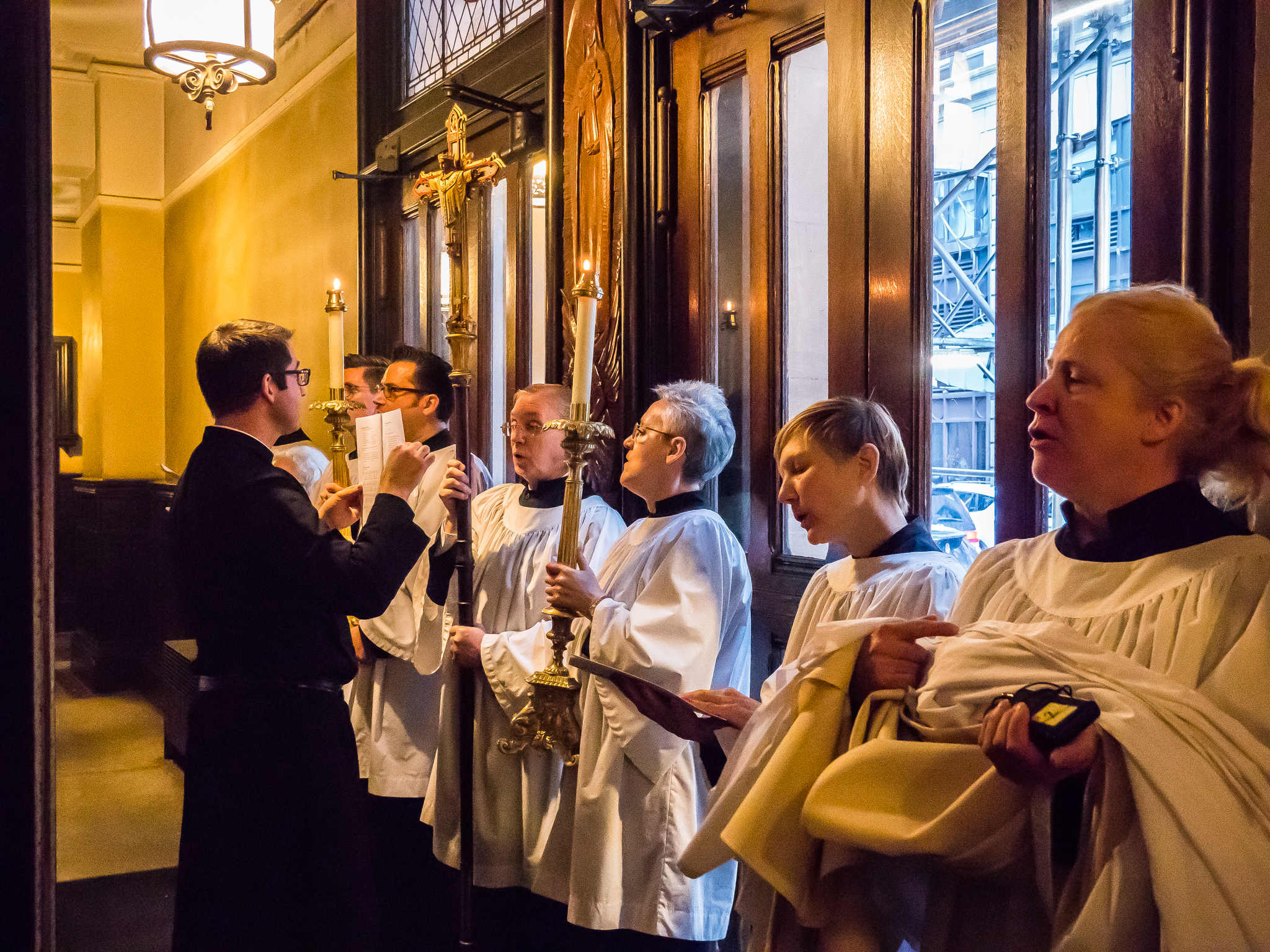 Servers and clergy, as a sign of their service, do not carry bulletins during processions; but they still like to sing. Father Jacobson assists after removing his vestments.  Photo by Ricardo Gomez
