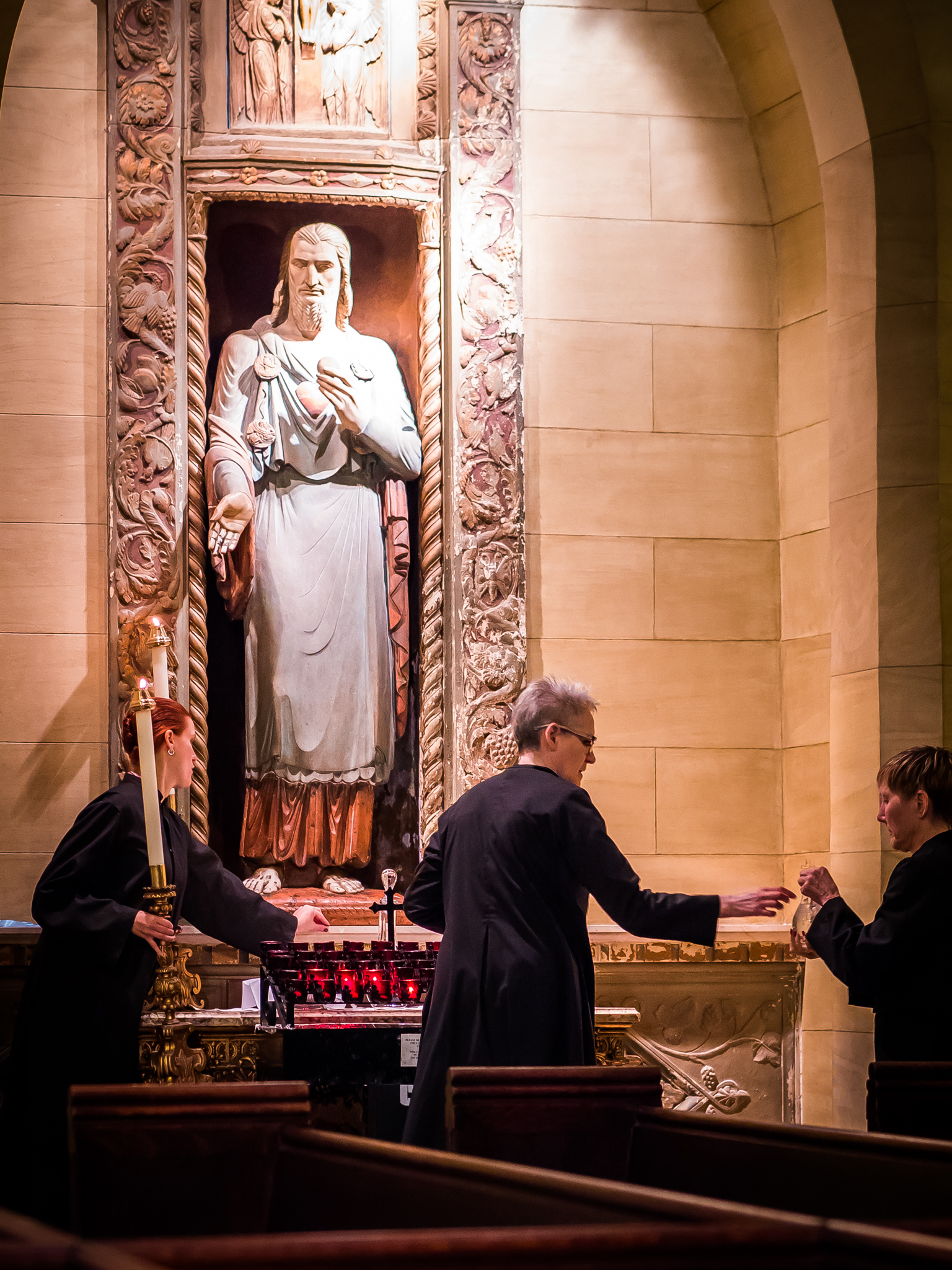 Before the Solemn Mass the servers place bread and wine at the Sacred Heart Shrine.  Photo by Ricardo Gomez