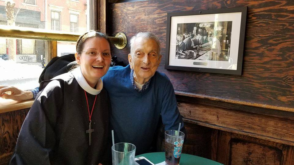 """Sr. Monica Clare, C.S.J.B., and Dick Leitsch at Julius on March 22, 2018. In the background is the photograph of Dick and his friends at the April 21, 1966 """"Sip-In"""" they organized. Following the regulations of the New York State Liquor Authority, they were refused service because they identified themselves as homosexuals.    Photo by Helen Buford"""