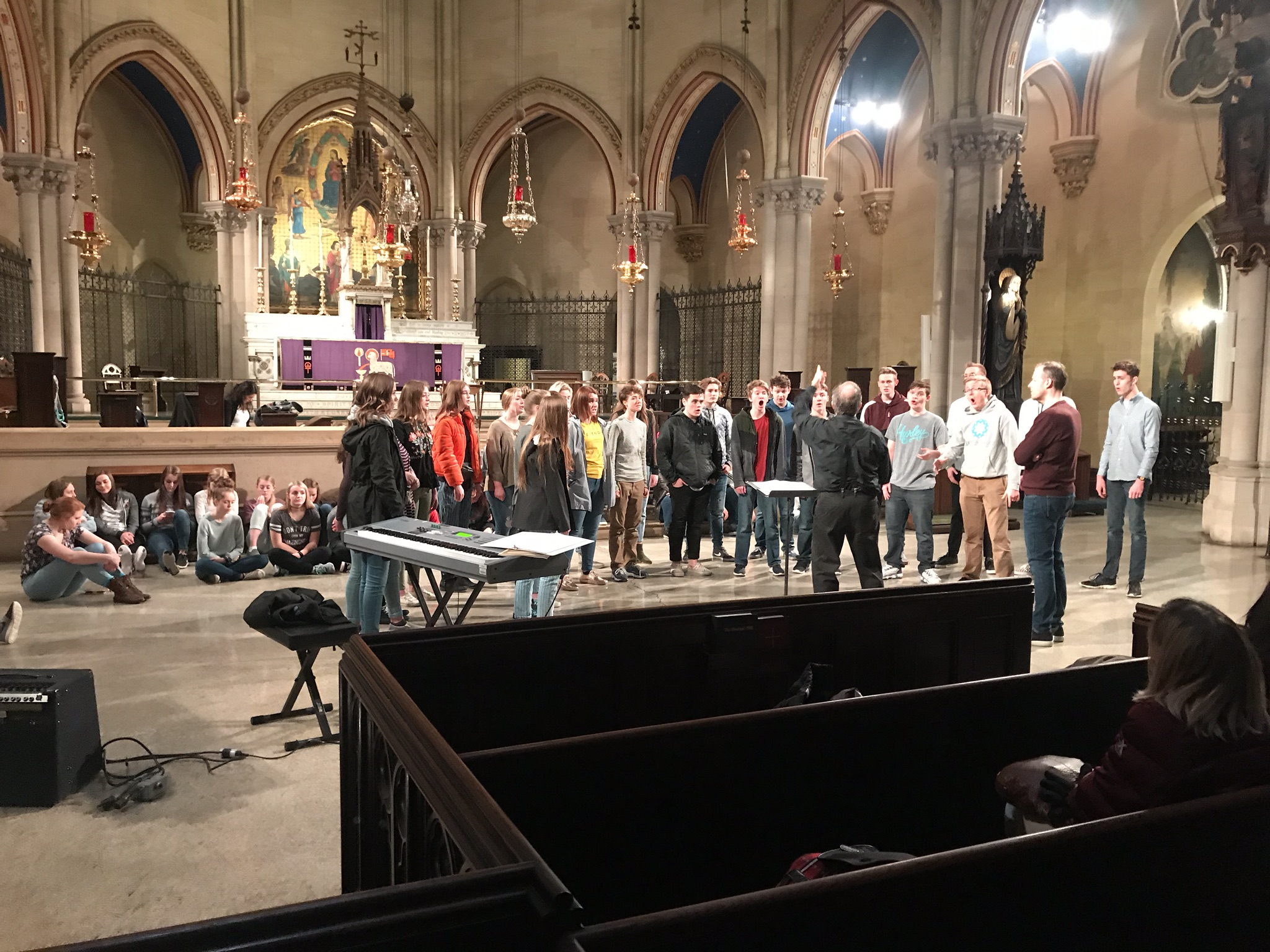Kent Tritle, director of cathedral music and organist at the Cathedral of St. John the Divine, conducts a rehearsal for the Bingham High School Chorus, South Jordan, UT, on Friday, March 23, 2019. This winter a number of high school groups are rehearsing in our church before performing here in the city. As the photograph was taken, the group was rehearsing Mozart's  Ave Verum Corpus.    Photo by the Rector