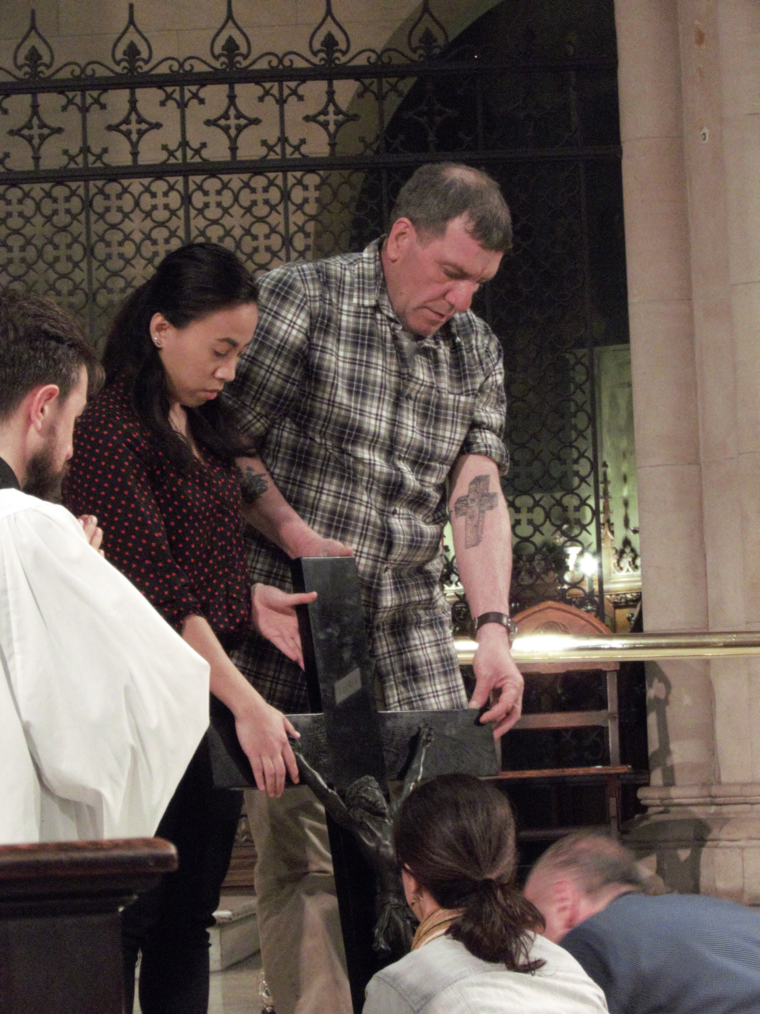 Two people kneel to venerate, then they will hold the cross for the next persons.  Photo by Damien Joseph SSF
