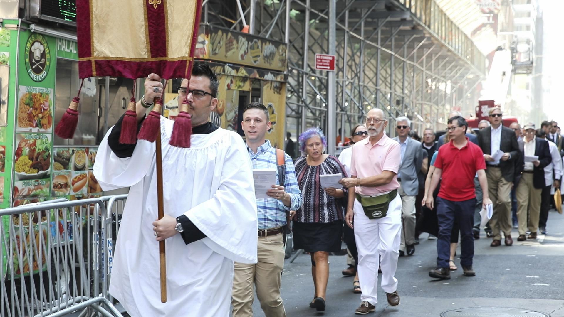 The congregation followed the Sacrament, led by a server bearing a banner.  Photo: Pamela Pasco