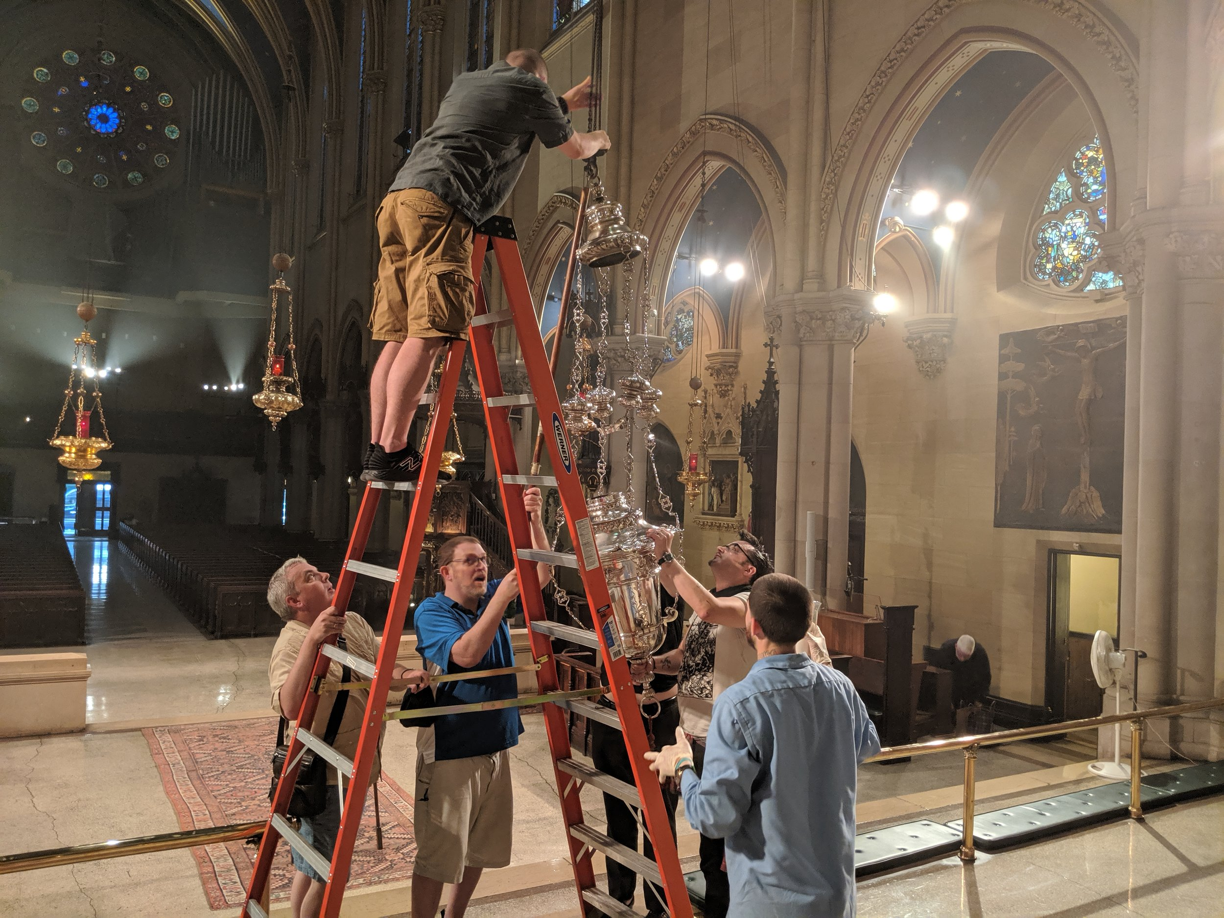 After the Solemn Mass on Sunday, July 21, 2019, the large silver lamp that signals the presence of the Sacrament was rehung after conservation by Matthew Hanlon Restorations.  Photo:  Grace Mudd