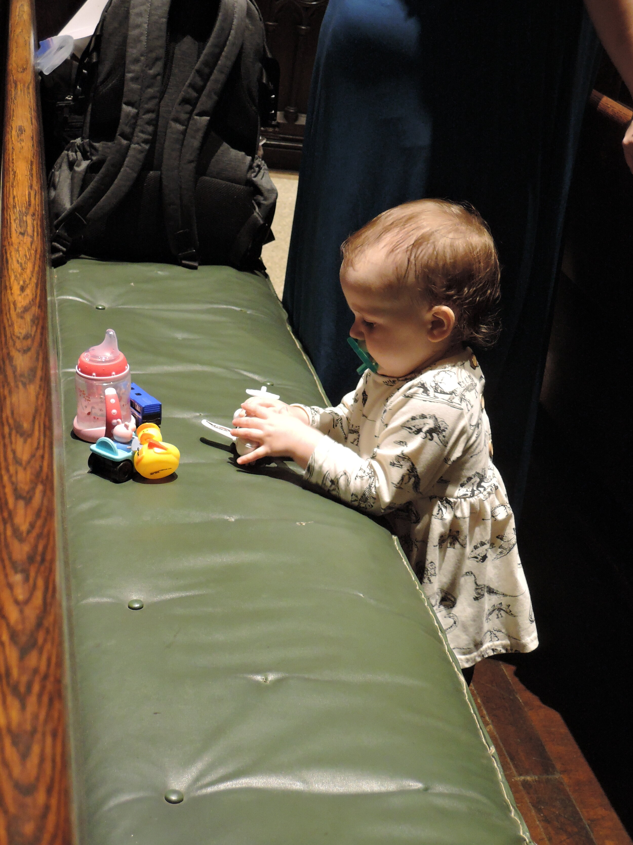 A young communicant during the sermon. Carried in her mother's arm, she came to the altar rail with her hand stretched out to receive the Bread. Photo: Grace Mudd